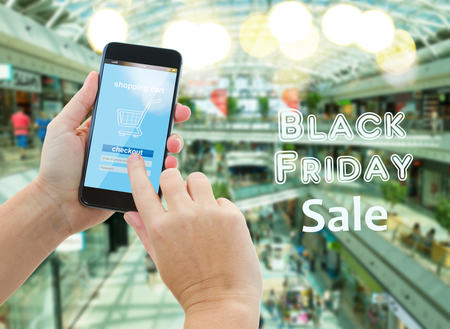 comercial: hand holding mobile smart phone with mobile shop  on comercial center blur background and black friday sale words