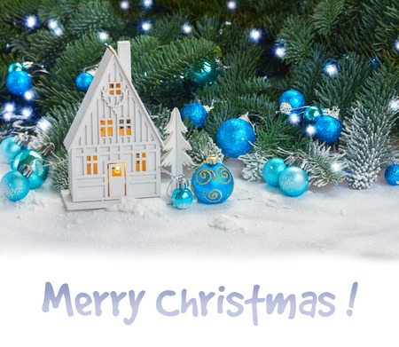 White christmas house with blue decorations in snow border on white and sample text Merry Christmas