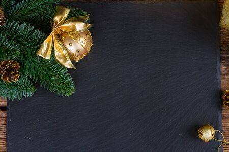 happy holidays: evergreen tree with golden ball and bell christmas frame on black background
