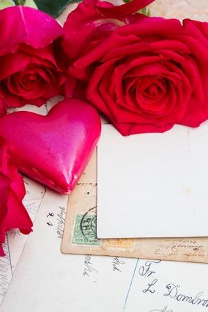 Postal vacía con el correo de la vendimia, corazón rosado y rosas frescas Foto de archivo - 49214877