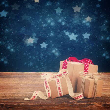 stary: Pile of Handmade gift boxes on wooden table, stary night at background, retro toned