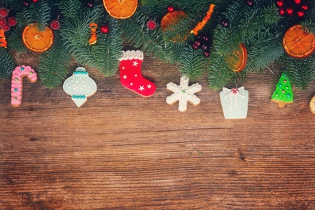 gingerbread cookies: christmas gingerbread cookies with fir tree border on wooden background, retro toned Stock Photo