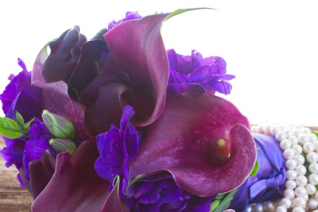 Bouquet of fresh calla lilly and eustoma flowers close up on wooden table isolated on white background