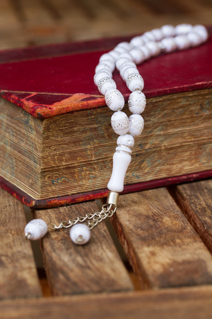nabi: Holy Quran book with white  beads over wooden table Stock Photo
