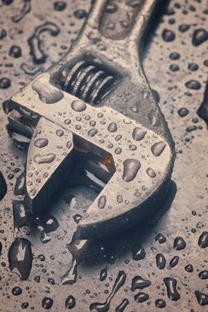 adjustable: Adjustable spanner  on black metal in water drops, retro toned