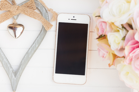 styled: styled desktop with modern phone, heart  and flowers Stock Photo