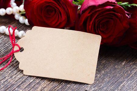 rosa flores frescas rojas con las perlas y la nota de papel vacía en la mesa de madera de cerca Foto de archivo