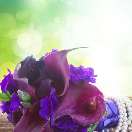 White Callas: Ramo de Lilly de la cala fresca y eustoma flores de cerca en la mesa de madera con fondo verde
