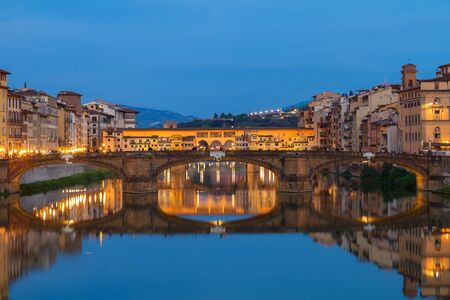 trinita: Ponte Santa Trinita bridge with reflection in the Arno River at night, Florence, Italy
