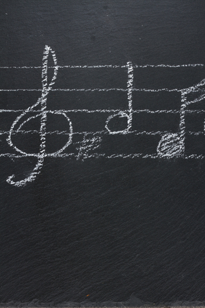 black backgound: White  music notes with treble clef  on black backgound, verticel shot