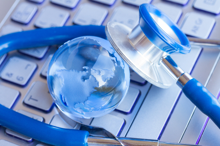 stetoscope: Stetoscope and glass globe on laptop keyboard - health care and enviroment concept