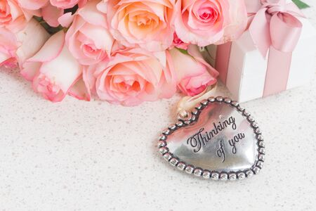 thinking of you: Thinking of You metal Heart with gift box and pink roses on white table