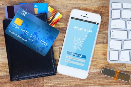 desk with internet store page on mobile  phone and wallet with plastic cards Archivio Fotografico