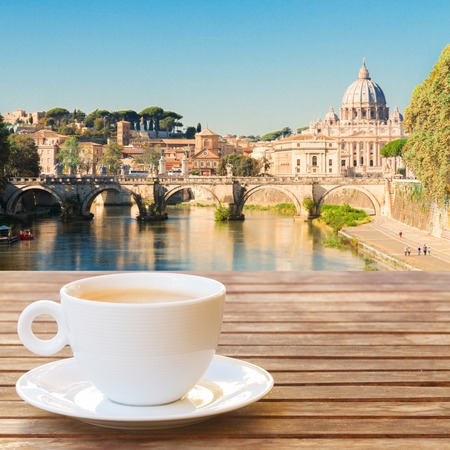Cup of coffee in Rome with view of Tiber river and st Peters cathedral, Italy