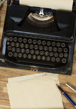 black vintage typewriter  on wooden table, copy space on aged paper, top view Reklamní fotografie - 53179355