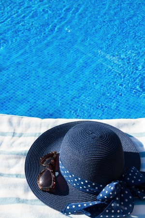sripes: towel and summer hat and sunglasses near pool  side Stock Photo