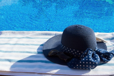sripes: towel and summer hat  near water of pool Stock Photo