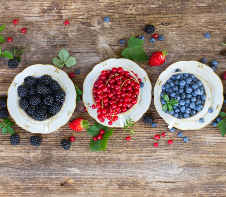 fresh red currant berry, blueberry  and blackberry with green leaves in cups on wooden table, top view