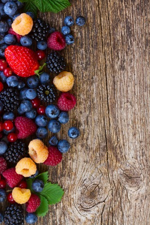 heap of fresh  berries mix on wooden tabletop with copy space Stock Photo