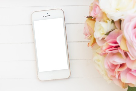 styled: styled white wooden desktop  with modern phone  and flowers