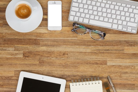 Office styled desktop frame with  coffee, mobile, tablet and keyboard