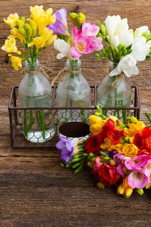 freesia: Fresh freesia flowers in vases  on wooden table  background