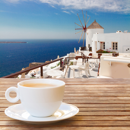 Cup of coffee with view of Windmill and blue sea at Oia, Santorini, Greece