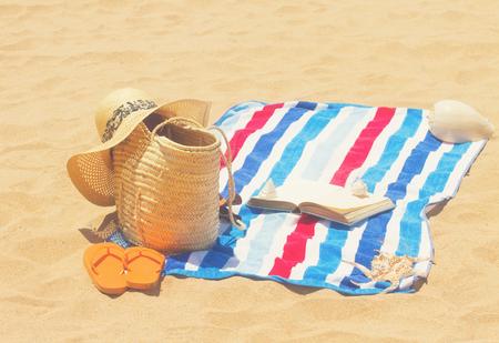 towel and sunbathing accessories on sandy beach, retro toned
