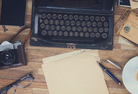 black vintage typewriter with supplies  on wooden table, copy space on aged paper, top view, retro toned