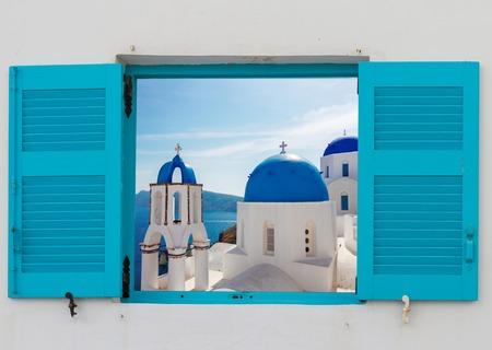 venster met uitzicht op de klassieke kerk met blauwe koepels, Oia, Santorini, Griekenland Stockfoto