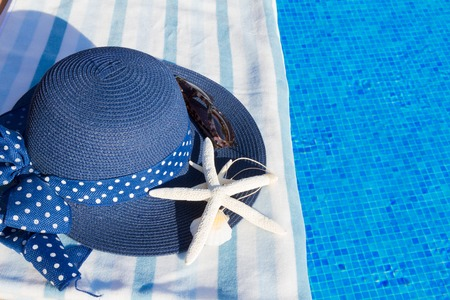 sripes: towel and summer hat with seashells near water of pool
