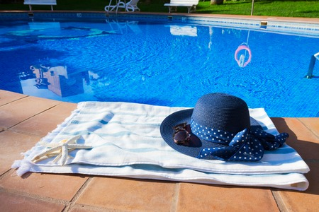 sripes: towel and summer hat  near pool at sunny summer day