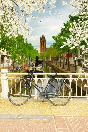 church tower: Bike on bridge and Canal with Old Church tower of Delft, Holland Stock Photo