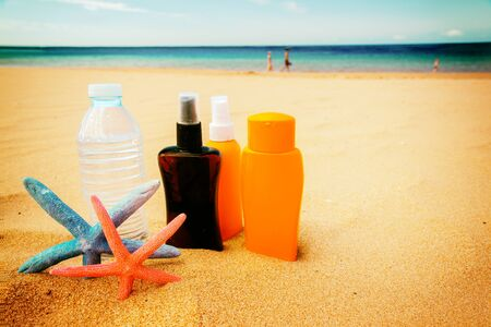 bottle of cool water with suntun creams on sandy beach by sea side, retro toned