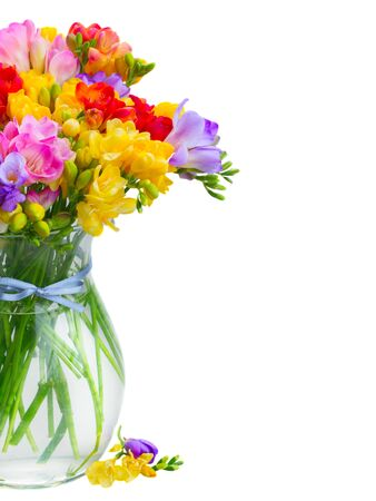 posy: Posy of fresh freesia flowers in glass vase close up  isolated on white background Stock Photo