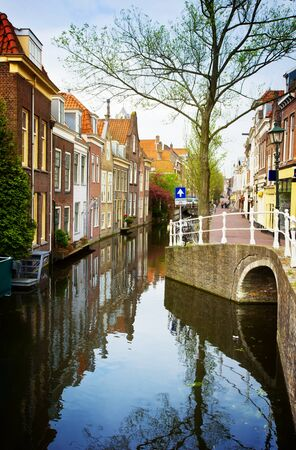 delft: colorful street with canals in old town  of Delft, Holland, retro toned