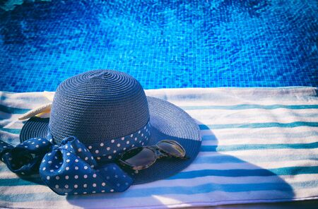 sripes: towel and summer hat  near water of pool, retro toned