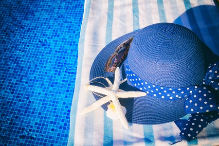 sripes: towel and summer hat with seashells near water of pool, retro toned