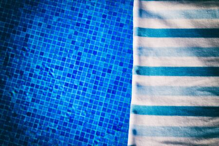 pool side: resort background with striped towel  near pool  side, , retro toned