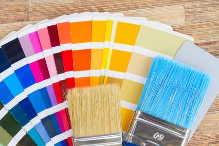 Color palette guide and brushes close up on wooden background