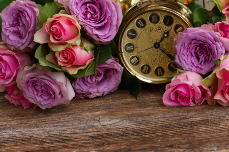aniversary: bouquet of pink and violet  fresh roses with golden vintage clock
