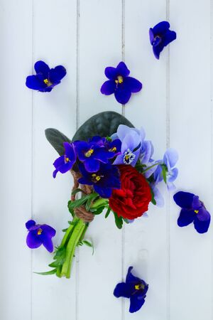 violets: Posy of violets, pansies and ranunculus on white wooden background