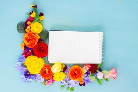 composition notebook: Flowers festive composition on blue wooden table with copy space on empty notebook Stock Photo