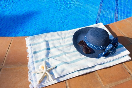 sripes: towel and summer blue hat  near pool at sunny summer day