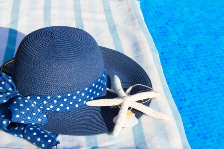sripes: towel and summer blue hat with seashells near water of pool