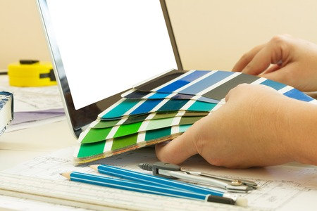 color consultant: designers working table - close up of designer hands holding colour charts, copy space on emptyy screen