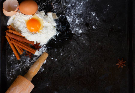 cooking utensil: raw baking ingredients with egg and spices  and pin on black background  with copy space Stock Photo