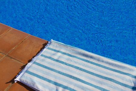 sripes: resort background with striped towel  near pool  clear blue  water