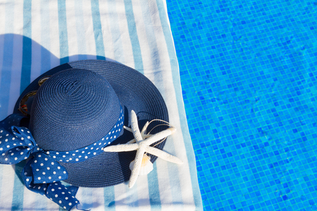 sripes: towel and summer blue hat with starfish near water of pool