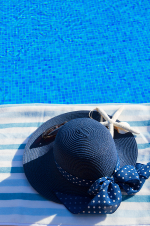 sripes: towel and summer blue hat with seashells near pool, copy space on blue water Stock Photo